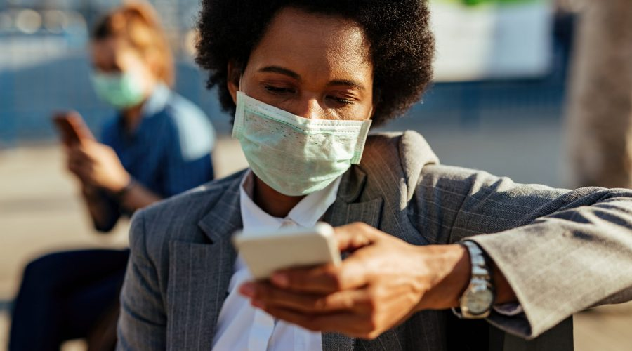 American businesswoman wearing face mask and texting on cell phone on the street.